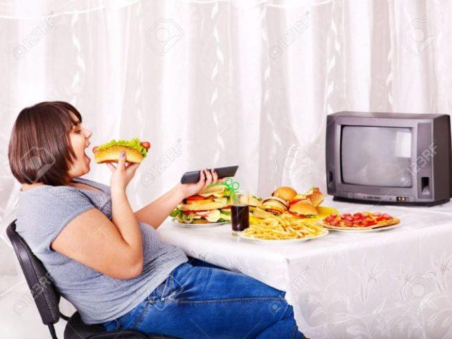 15290486-Sobrepeso-mujer-comiendo-comida-r-pida-y-viendo-la-televisi-n–Foto-de-archivo